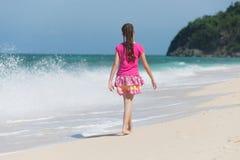 Une petite fille marchant sur une plage Image libre de droits