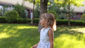 Une petite fille mignonne dans une robe de lumière d'été jouant avec des bulles de savon en parc banque de vidéos