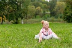 Une petite fille mignonne dans une belle robe et des espadrilles jouant dedans Photo stock