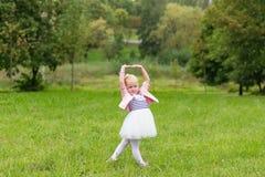 Une petite fille mignonne dans une belle robe et des espadrilles jouant dedans Photos libres de droits