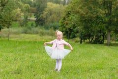 Une petite fille mignonne dans une belle robe et des espadrilles jouant dedans Photographie stock