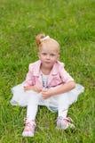 Une petite fille mignonne dans une belle robe et des espadrilles jouant dedans Image stock