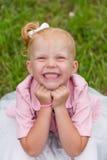 Une petite fille mignonne dans une belle robe et des espadrilles jouant dedans Images stock