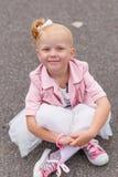Une petite fille mignonne dans une belle robe et des espadrilles jouant dessus Image stock