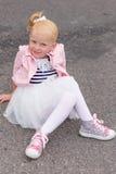 Une petite fille mignonne dans une belle robe et des espadrilles jouant dessus Photo libre de droits