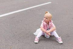 Une petite fille mignonne dans une belle robe et des espadrilles jouant dessus Images libres de droits