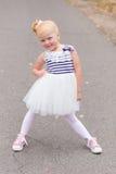 Une petite fille mignonne dans une belle robe et des espadrilles jouant dessus Photo stock