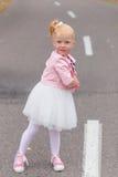 Une petite fille mignonne dans une belle robe et des espadrilles jouant dessus Images stock