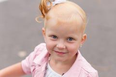 Une petite fille mignonne dans une belle robe et des espadrilles jouant dessus Photographie stock