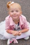 Une petite fille mignonne dans une belle robe et des espadrilles jouant dessus Image libre de droits