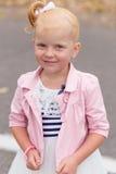 Une petite fille mignonne dans une belle robe et des espadrilles jouant dessus Photos stock