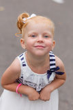 Une petite fille mignonne dans une belle robe et des espadrilles jouant dessus Photos libres de droits