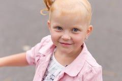 Une petite fille mignonne dans une belle robe et des espadrilles jouant dessus Photographie stock libre de droits