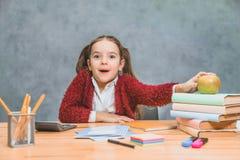 Une petite fille mignonne espi?gle a l'amusement tout en comptant sur les livres ?pais sur un fond gris Ses cheveux sont faits de images stock