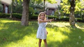 Une petite fille mignonne jouant avec des bulles de savon en parc sur l'herbe verte banque de vidéos