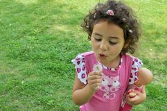 Une petite fille mignonne a l'amusement dans un jardin image libre de droits