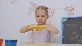 Une petite fille mignonne s'asseyant ? la table dans le dessin de la pi?ce d'enfants avec des peintures de doigt a souill? ses ma clips vidéos