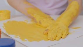 Une petite fille mignonne s'asseyant ? la table dessine sur le papier avec les peintures lumineuses de doigt, plongeant ses doigt clips vidéos
