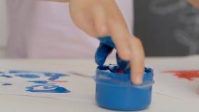 Une petite fille mignonne s'asseyant ? la table dessine sur le papier avec les peintures lumineuses de doigt, plongeant ses doigt banque de vidéos