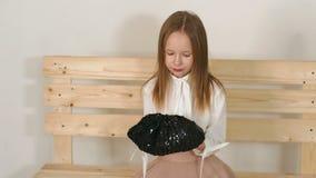 Une petite fille mignonne s'assied sur un banc en bois sur un fond blanc dans le studio banque de vidéos