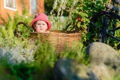 Une petite fille mignonne s'assied sur un foin dans un panier dans le jardin Photos libres de droits
