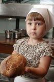 Une petite fille montre le pain rustique Image libre de droits