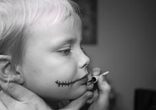 Une petite fille obtenant la peinture de clown a mis dessus photographie stock libre de droits