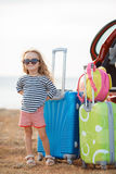 Une petite fille part en voyage sur une voiture rouge Photo stock