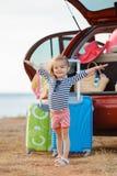 Une petite fille part en voyage sur une voiture rouge Photos stock