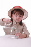 Une petite fille pleut à torrents l'eau d'une cruche dans une glace Photos stock