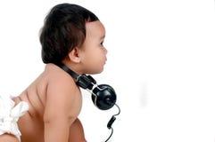 une petite fille potelée avec des écouteurs   Photographie stock libre de droits