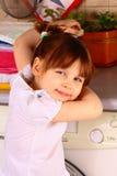 Une petite fille près de la machine à laver Photo stock
