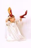 Une petite fille retient de grandes chaussures Photographie stock libre de droits