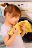Une petite fille retient un essuie-main après lavage Photographie stock libre de droits