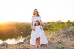 Une petite fille riante de sourire avec les cheveux bruns bouclés a habillé la robe courte blanche avec la jeune belle mère dans  photo stock