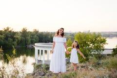 Une petite fille riante de sourire avec les cheveux bruns bouclés a habillé la robe courte blanche avec la jeune belle mère dans  photographie stock libre de droits