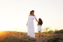 Une petite fille riante de sourire avec les cheveux bruns bouclés a habillé la robe courte blanche avec la jeune belle mère dans  images libres de droits