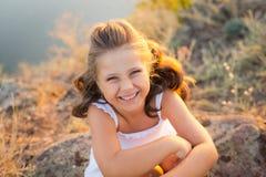 Une petite fille riante de sourire avec les cheveux bruns bouclés a habillé la robe courte blanche se reposant sur les pierres à  photos stock