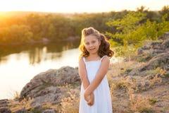 Une petite fille riante de sourire avec les cheveux bruns bouclés a habillé la robe courte blanche sur les pierres à la rivière l images libres de droits