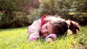 Une petite fille roule dans l'herbe banque de vidéos