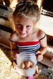 Une petite fille rurale mignonne tenant un seau en plastique avec des oeufs photographie stock libre de droits