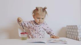 Une petite fille s'asseyant à la concentration de table peint avec l'aquarelle sur le papier banque de vidéos
