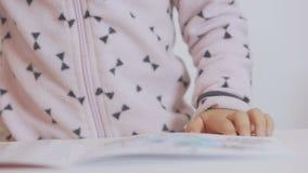 Une petite fille s'asseyant à la concentration de table peint avec l'aquarelle sur le papier clips vidéos