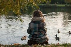 Une petite fille s'asseyant d'un côté de lac, regardant les canards de l'eau et d'alimentation Photographie stock libre de droits