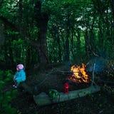 Une petite fille s'asseyant par le feu dans la forêt Image libre de droits