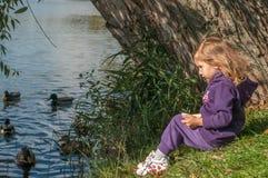 Une petite fille s'asseyant sur des canards d'un côté et d'alimentation de lac Photographie stock