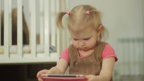 Une petite fille s'asseyant sur le plancher utilise une tablette, touchant son doigt sur l'écran tactile banque de vidéos