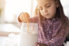 Une petite fille s'assied dans la cuisine à côté d'une boîte de farine Elle prend la farine avec une cuillère Photos stock