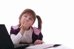 Une petite fille s'assied près de l'ordinateur portatif Photos stock