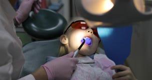 Une petite fille s'assied sur une chaise dentaire avec une bouche ouverte banque de vidéos